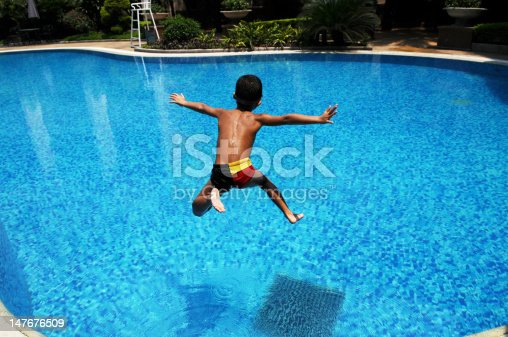 A Chinese little boy jumps into the blue,clear water in a swimming pool for cool in a hot summer day.