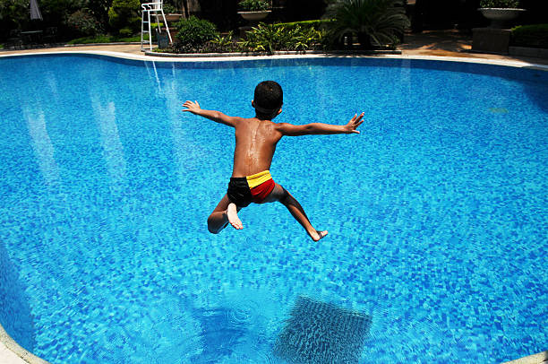 The asian boy jumps into   blue water A Chinese little boy jumps into the blue,clear water in a swimming pool for cool in a hot summer day. taking the plunge stock pictures, royalty-free photos & images