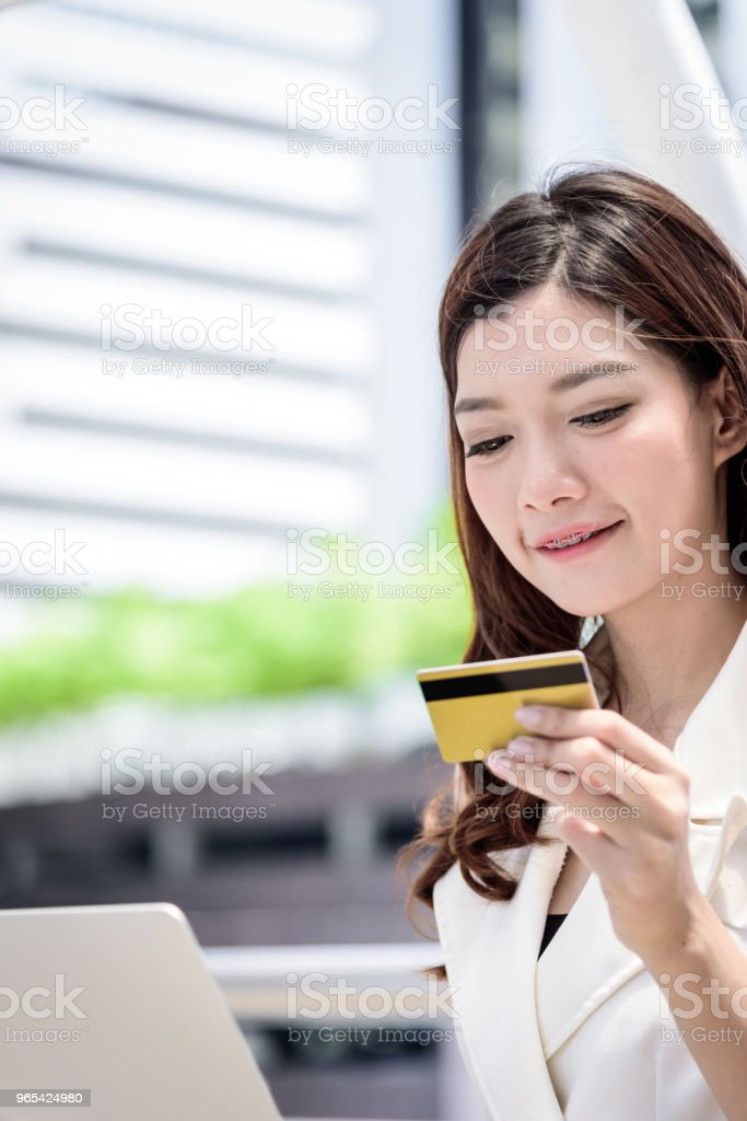 The asian business woman has shopping and buying with credit card from outside office with building and city background. zbiór zdjęć royalty-free