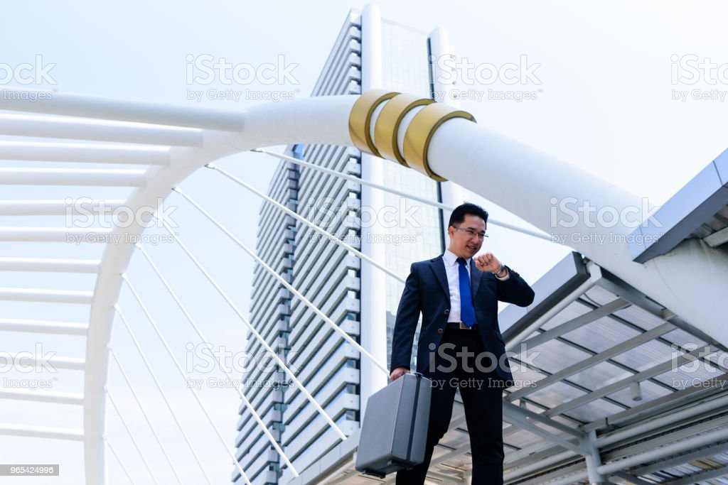 The asian businessman has holding a black bag and looking on watch in hurrying time. royalty-free stock photo