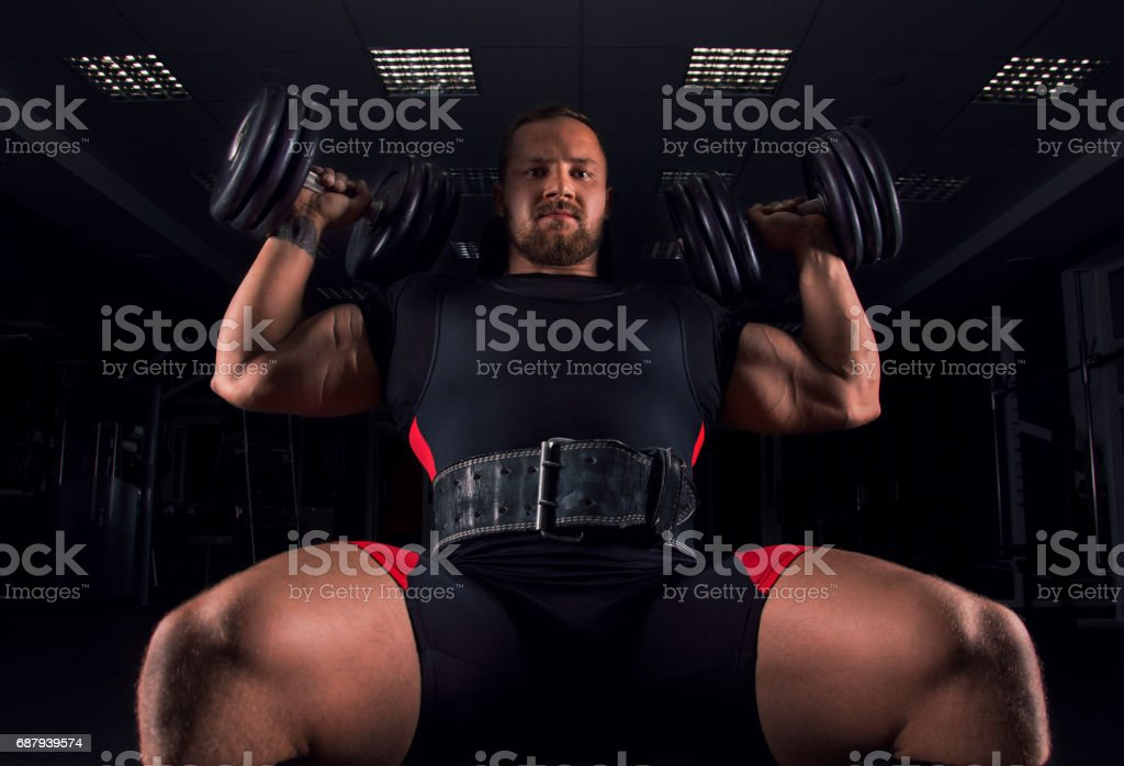 The athlete sits on a bench and does an exercise called military press stock photo