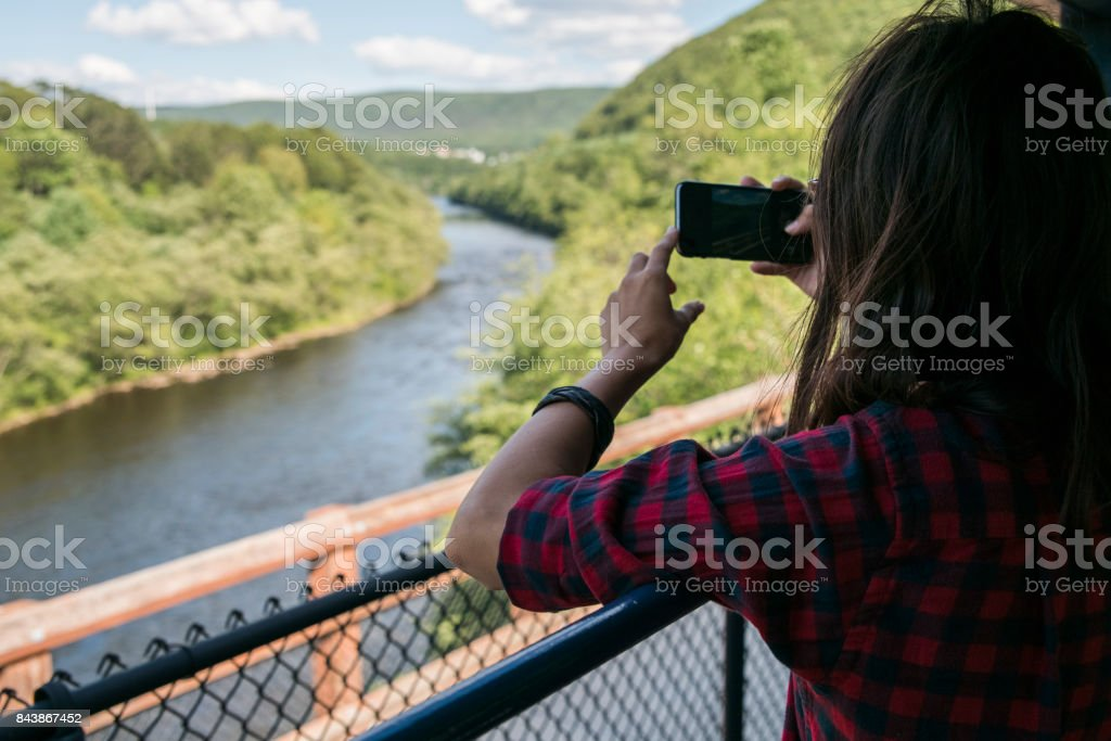 The attractive 15-years-old teenager girl enjoy the train ride through the scenic landscapes. stock photo