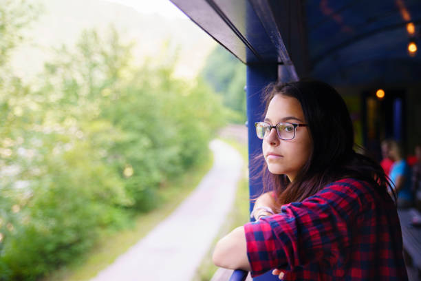 The attractive 15-years-old teenager girl enjoy the train ride through the scenic landscapes. - foto stock