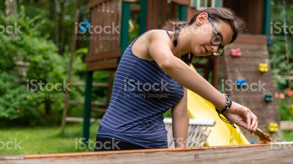 The attractive 15-years-old teenager girl painting the fence at the backyard stock photo