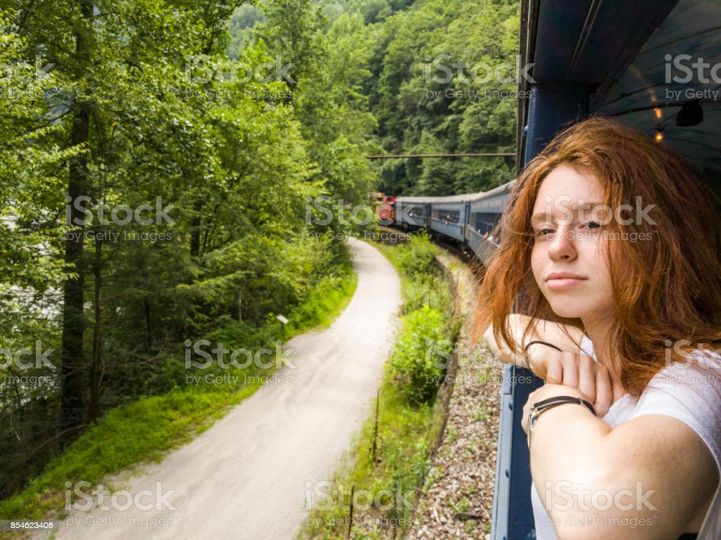The attractive 17-years-old teenager girl enjoy the train ride through the scenic landscapes. - foto stock