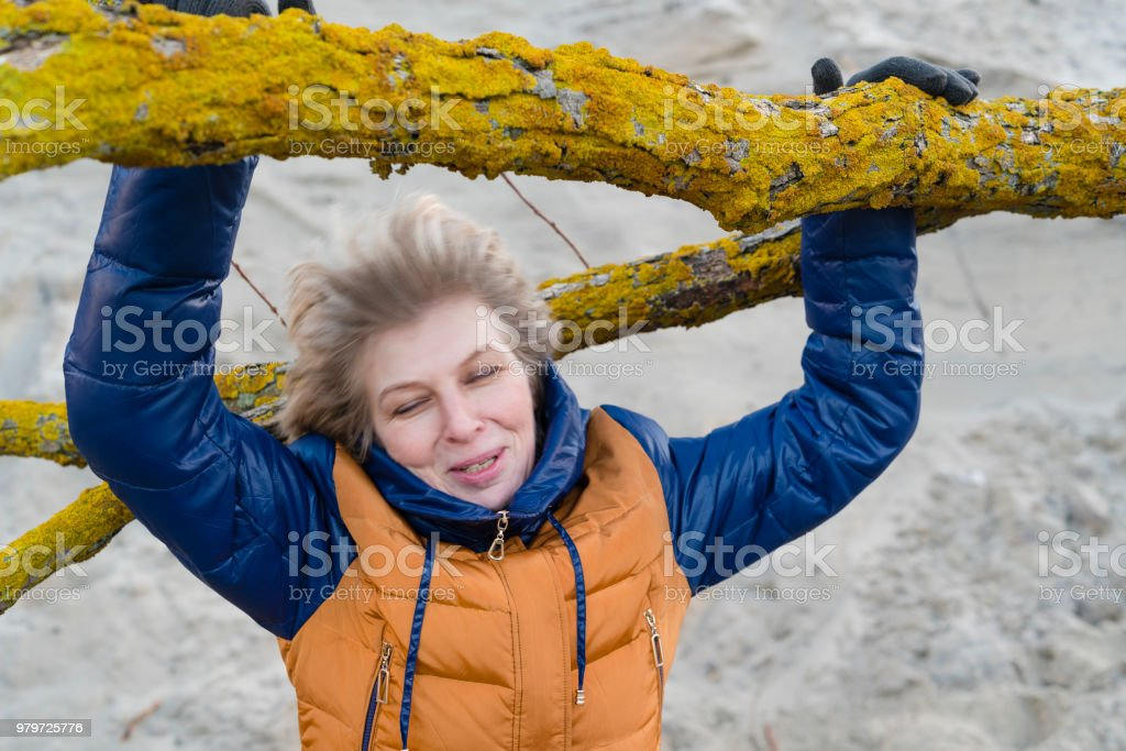 The attractive 50 years old mature woman resting at the beach of the Baltic sea stock photo