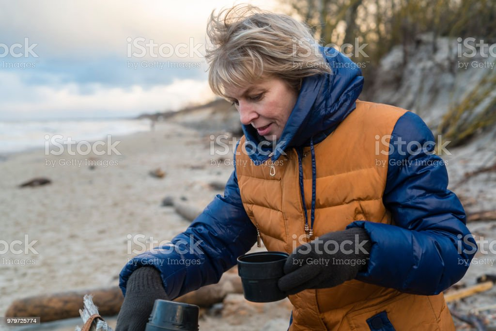 The attractive active 50 years old mature woman drinking the hot tea from thermos at the winter's beach of the cold Baltic Sea stock photo