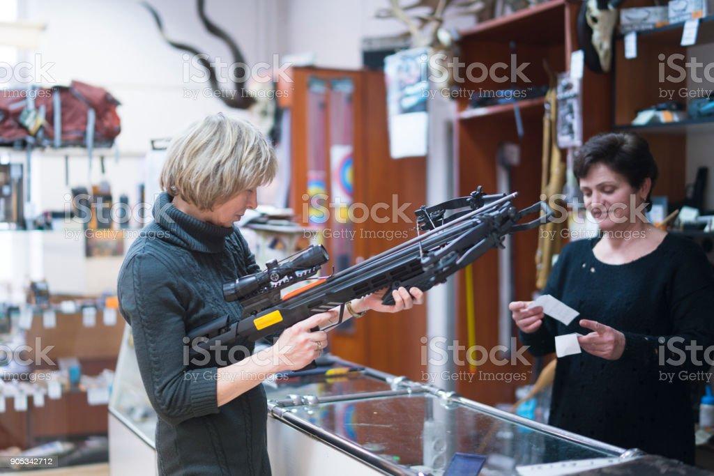 La blonde mature, âgé de 50 ans femme attirante examinant l'arbalète dans le magasin de chasse au petit, avec l'aide de la femme - vente persone. - Photo