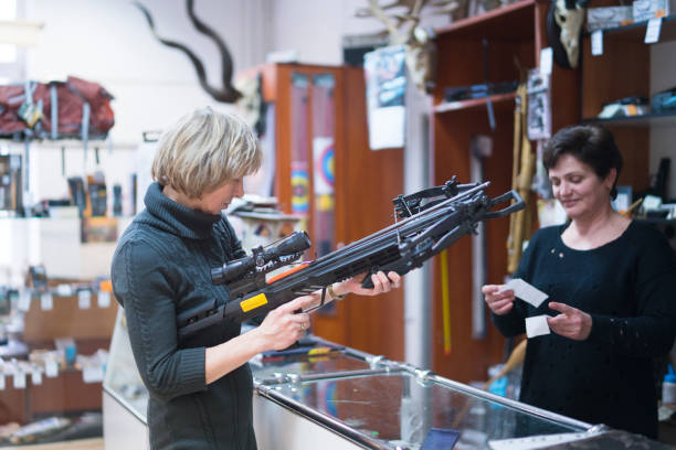 the attractive blonde mature, 50-years-old woman examining the crossbow in the small hunting store, with assistance of the woman - sales persone. - crossbow stock pictures, royalty-free photos & images