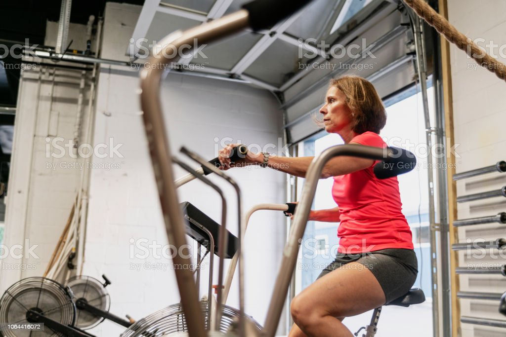 The attractive senior, 55-years-old, Latino woman doing a workout on the exercise bike in the gym stock photo