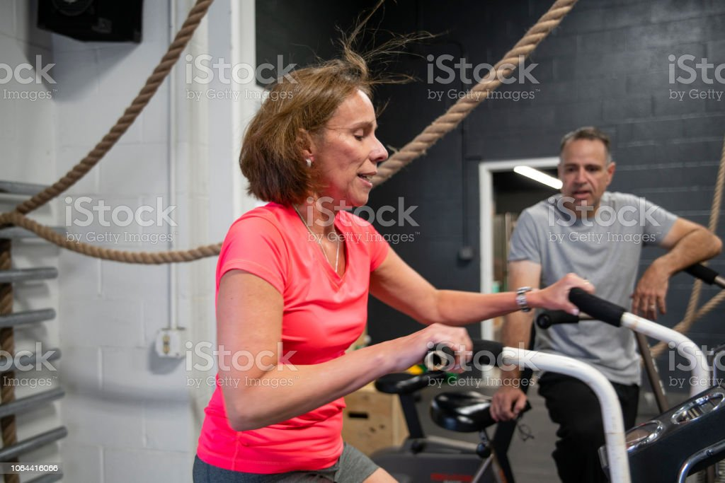 The attractive woman doing a workout on the exercise bike in the gym under the supervision of the coach, the senior 55-years-old Cuban Hispanic man. stock photo