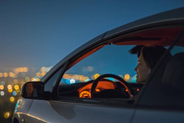 la jolie femme s'asseoir dans la voiture sur le fond de la ville. nuit - voiture nuit photos et images de collection