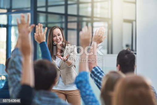 Shot of a group of people raising their hands in a seminar
