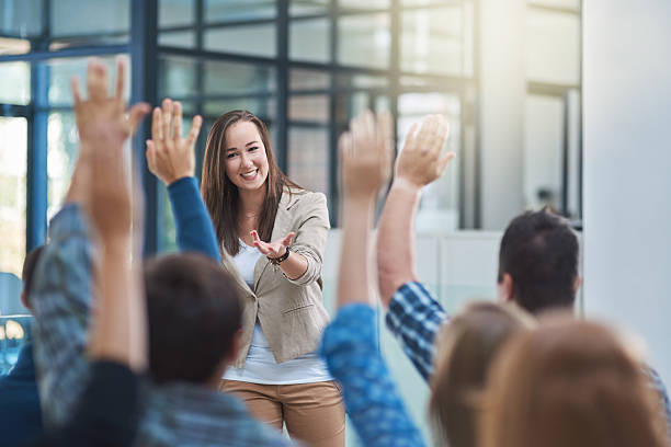 The audience has the answer Shot of a group of people raising their hands in a seminar presenter stock pictures, royalty-free photos & images