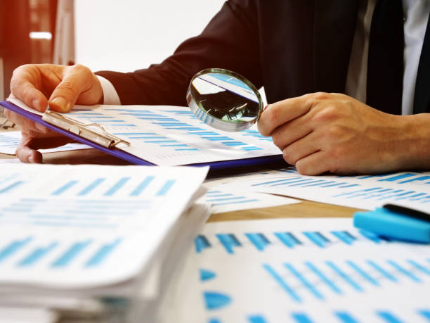 The auditor makes audit and verifies the report using a magnifying glass. stock photo