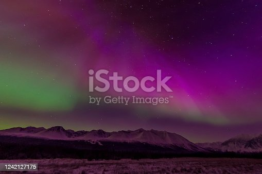 The aurora borealis is a natural light display in the sky particularly in the high latitude of the Arctic regions, caused by the collision of energetic charged particles with atoms in the high altitude atmosphere (thermosphere). Major solar flare causing great Aurora borealis over Kluane National Park, Yukon, Canada. Coronas form of aurora.