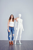 Studio shot of a young woman posing next to a mannequin against a grey background