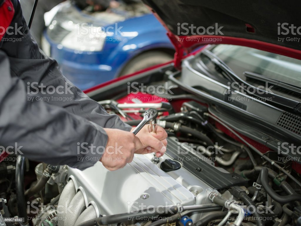 The auto mechanic checks the car under the hood. stock photo