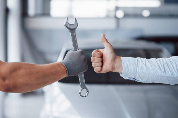 Der Automechaniker hält den Schlüssel in der Hand des Kunden und hebt den Daumen nach oben. Gut gemacht – Foto
