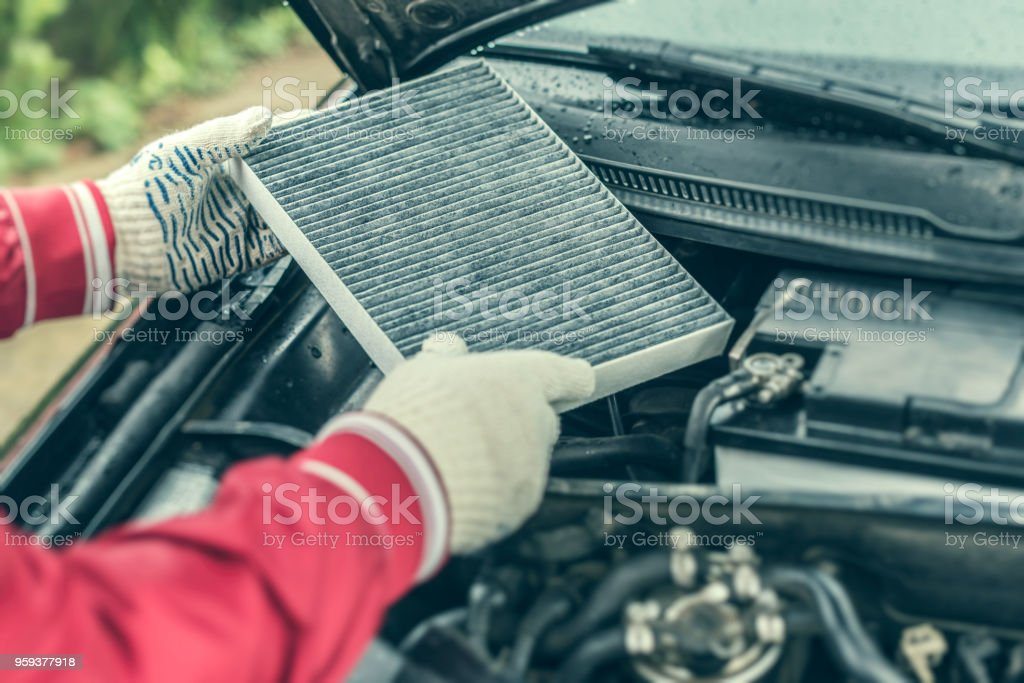 The auto mechanic replaces the car's interior filter stock photo