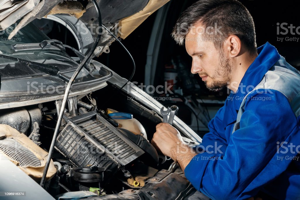 The auto mechanic works in the garage. Repair service. Maintenance of...