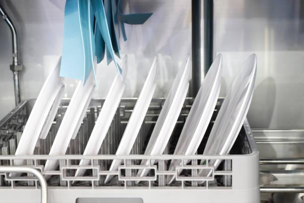El lavavajillas automático con platos blancos limpios i - foto de stock