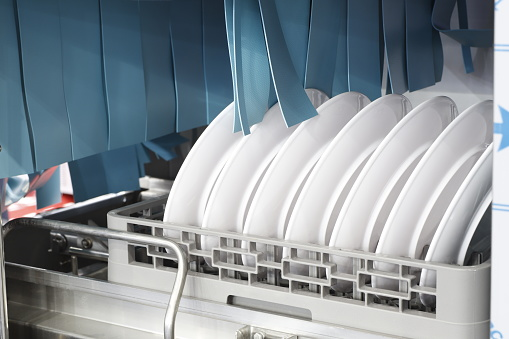The automatic dishwasher with white clean dishes in basket .For restaurant. Business industrial background