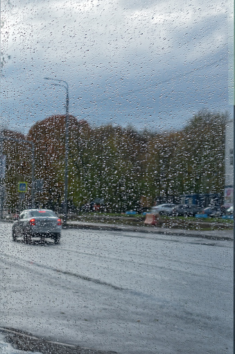 The autumn. A rain. A raindrops on blurred reflections background in street mirror.