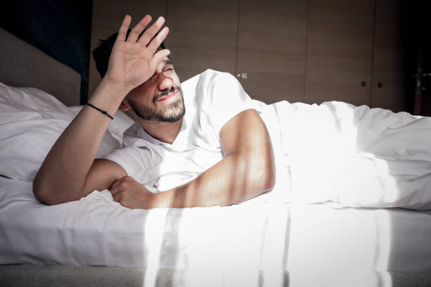 The awakening is stressful A man wakes up in bed under stress aftereffect stock pictures, royalty-free photos & images
