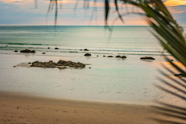 The azure coast, the beach on the island of Thailand, the sunset, the rocks by the shore and the blurred palm tree as a natural border of the landscape, Thailand – zdjęcie