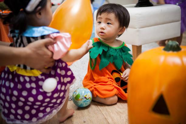 das baby genießt eine halloween-party. - teppich hellblau stock-fotos und bilder