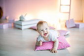 Little boy under the age of 1 year lies in a room on a pink pillow on his birthday