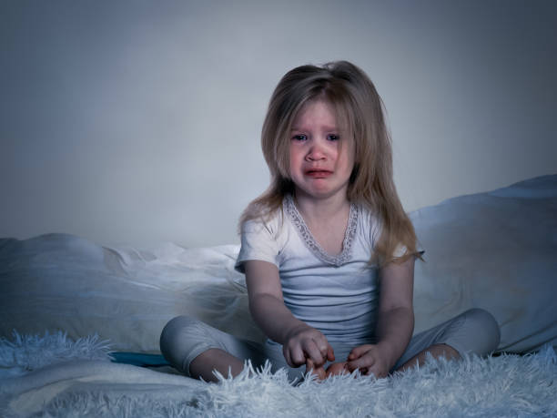 The baby is crying. A little girl in bed for the night stock photo