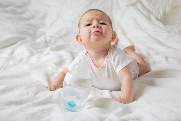 The baby is drooling and teething. He lies on a white bed and pulls his hands to a bottle of water. Cheerless and naughty child. stock photo