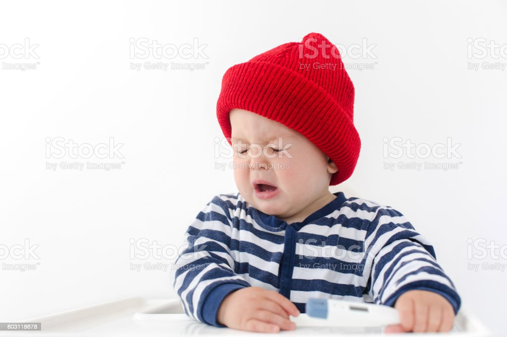 The baby sneezes with thermometer stock photo