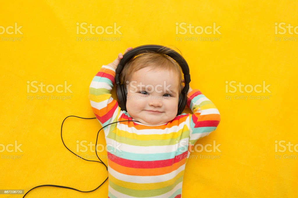 the baby with headphones on a yellow background stock photo