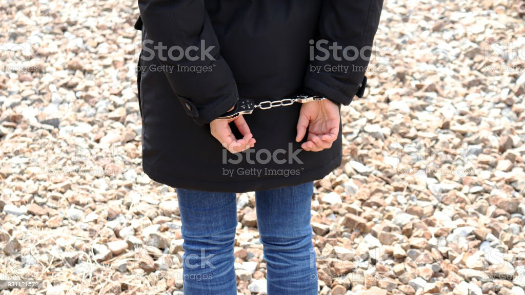 The back of a criminal in handcuffs. Concept of criminal arrest. stock photo