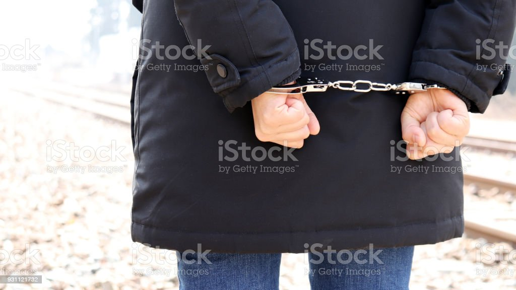 The back of a criminal in handcuffs. stock photo