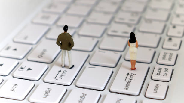 The back of a miniature man standing on an enter key and a miniature woman standing on a backspace key. The concept of a gender gap. The back of a miniature man standing on an enter key and a miniature woman standing on a backspace key. The concept of a gender gap. discriminatory stock pictures, royalty-free photos & images