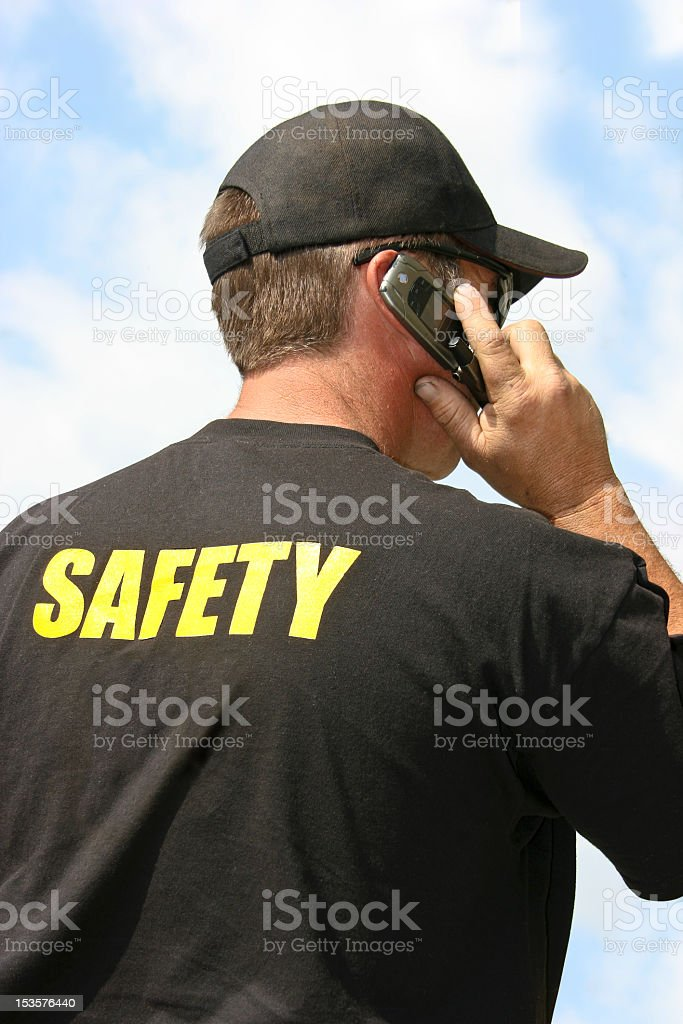 The back of a security agent who is on the phone stock photo