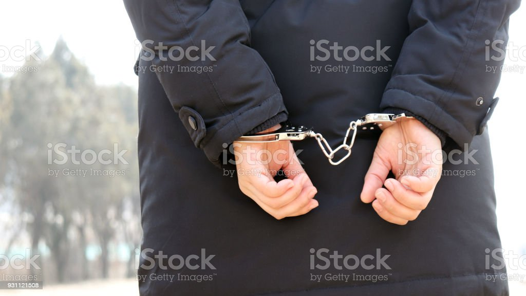 The back of a woman in handcuffs. stock photo
