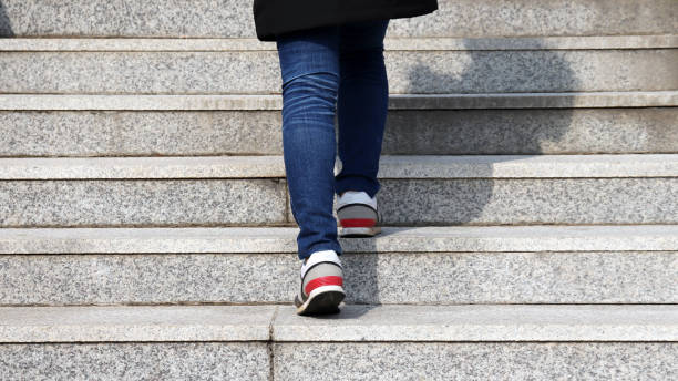 The back of a woman's leg as she climbs the stairs. stock photo