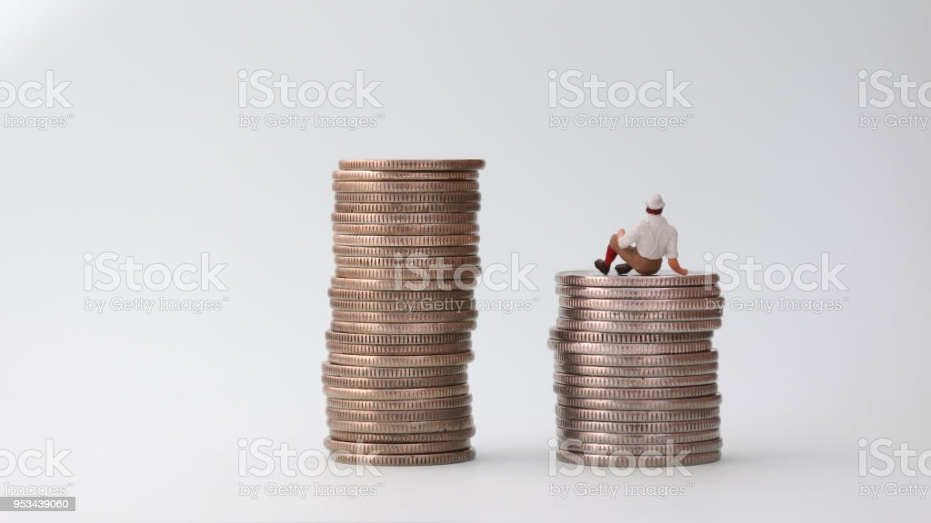 The back of miniature man sitting on coins. stock photo