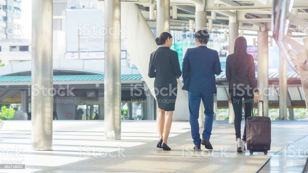 The back position of group smart business people of man and woman walk together at the outdoor pedestrian walkway space in the morning. royalty-free stock photo