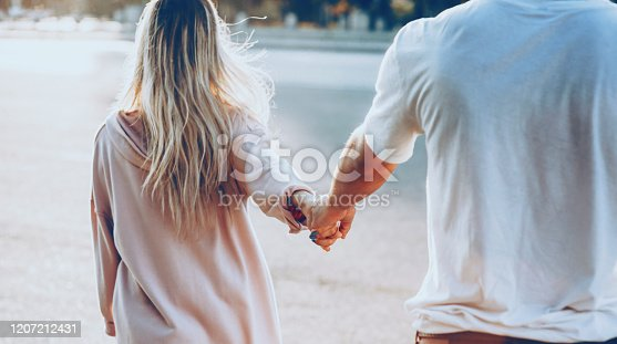 The back view of a young caucasian couple dressed in white walking hand in hand during sun is warming them