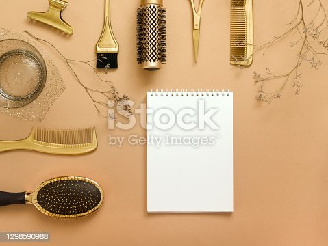 The background is beige with hairdressing tools, an empty white notebook, and dried flowers. Gold hair accessories, pattern with copy space.