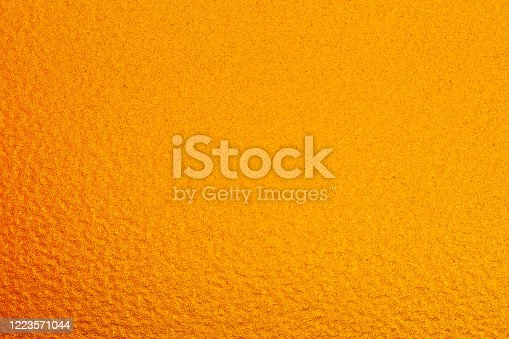 The background is dark yellow. It have a rough surface.