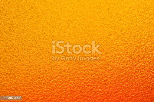 Horizontal image. The background that has only a slight orange shading to a yellow color. It have a rough surface.