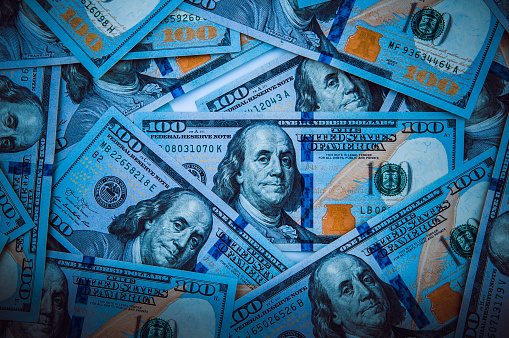 693363558 istock photo The background of a one hundred dollar bill. Style blue light. 1211941728