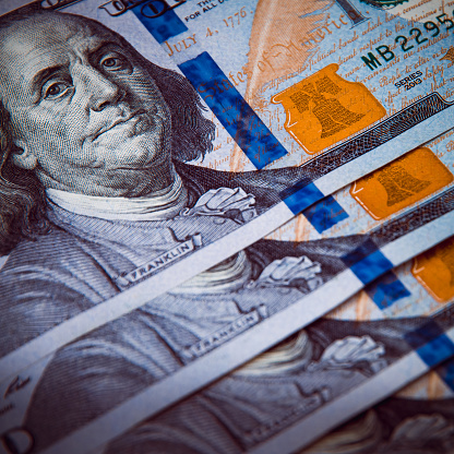 693363558 istock photo The background of a one hundred dollar bill. Style blue light. 1211942069